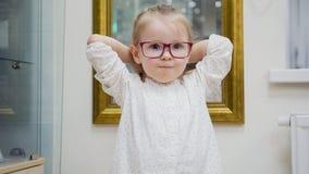 Portret van kindmeisje in glazen - het jonge geitje probeert manier medische glazen winkelend in oftalmologiekliniek Royalty-vrije Stock Foto's