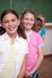 Portret van klasgenoten die in een rij stellen stock foto