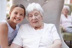 Portret van Kleindochter Bezoekende Grootmoeder in Pensioneringshuis stock foto