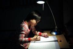 Portret van kleine Aziatische meisjes die haar thuiswerk doen onder ligh royalty-vrije stock foto's
