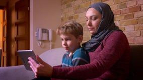 Portret van kleine jongen en zijn en geamuseerde moslimmoeder die in hijab het letten op film op tablet thuis worden opgewonden stock footage