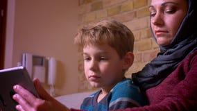 Portret van kleine jongen en zijn moslimmoeder in hijab het letten op film op tablet en thuis het bespreken stock videobeelden