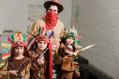 portret van kleine jongens in inheemse kostuums en vader in hoed en rode bandana die camera bekijken royalty-vrije stock afbeeldingen