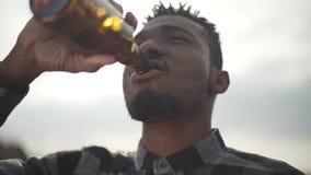Portret van knap Afrikaans Amerikaans mens het drinken bier die de camera in openlucht onderzoeken De zonnige lichte hemel in stock videobeelden