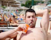 Portret van knap jonge mens het drinken sap op de pool Stock Fotografie