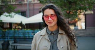 Portret van knap meisje dat zonnebril draagt die in openlucht bevinden zich glimlachend stock video