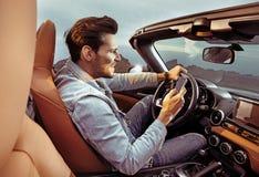 Portret van knap, rijke man die zijn convertibele auto drijven royalty-vrije stock afbeelding