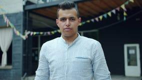 Portret van knappe Arabische kerel in openlucht met ernstig gezicht die camera bekijken stock videobeelden