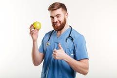 Portret van knappe arts in blauwe laag die camera bekijken Stock Foto