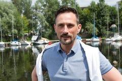 Portret van knappe atractive zakenman dichtbij van rivier met boten Riviercruise voor succesvolle mensen stock foto