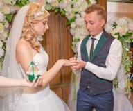 Portret van knappe bruidegom die trouwring op bruidenhand zetten Stock Foto