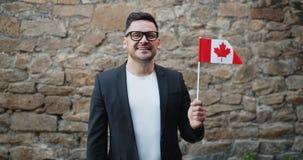 Portret van knappe gebaarde kerel die Canadese vlag golven die in openlucht zich alleen bevinden stock videobeelden