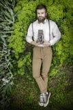 Portret van knappe jongelui bij de kostuummens met camera het laing in groen gras en het ooking bij camera De mensencamera die Sc Royalty-vrije Stock Afbeeldingen