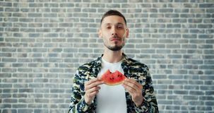 Portret van knappe kerel die watermeloen eten en op bakstenen muurachtergrond glimlachen stock footage
