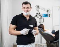 Portret van knappe mannelijke tandarts die tandhulpmiddelen houden - sonde en spiegel op tandkantoor tandheelkunde royalty-vrije stock afbeelding