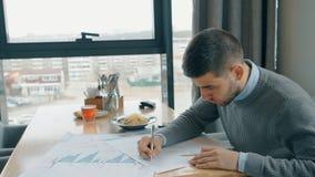 Portret van knappe zakenman die financiële grafieken in koffie verbeteren stock video