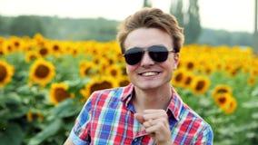 Portret van koele mannelijk-landbouwer het dansen pret op zonnebloemengebied, tevreden en positief op zonsondergang De landbouwco stock videobeelden
