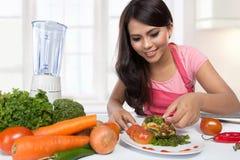 Portret van kokende vrouw in keuken Stock Afbeelding