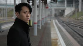 Portret van Koreaanse zakenman die messege buiten op raiway post typt stock footage
