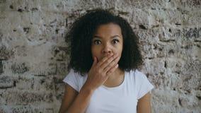 Portret van krullende gemengde actief en rasvrouw die onderzoekend camera op bakstenen muurachtergrond verrassen benieuwd zijn