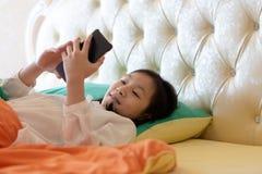 Portret van leuk Aziatisch meisje op bed terwijl gebruikssmartphone met att stock foto