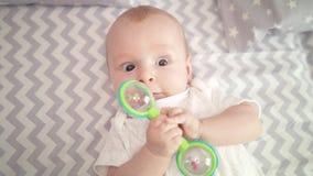 Portret van leuk babyjongen het spelen stuk speelgoed Het leuke kind spelen met rammelaar op bed stock videobeelden