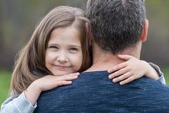 Portret van leuk die meisje in vader` s wapens wordt gehouden Gelukkige houdende van familie Concept Vaderdag Familievakantie en  stock fotografie