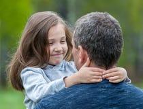 Portret van leuk die meisje in vader` s wapens wordt gehouden Gelukkige houdende van familie Vader en zijn het meisje van het doc stock afbeelding