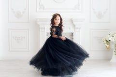 Portret van leuk glimlachend meisje in zwarte prinses pluizige kleding stock foto's