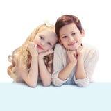 Portret van leuk glimlachend twee kinderen die bij de lijst zitten stock foto
