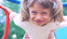 Portret van leuk Kaukasisch littemeisje die witte kleding met bloemen dragen die op aapbars hangen op een de zomerdag Meisje royalty-vrije stock afbeeldingen
