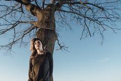 Portret van leuk meisje dichtbij een boom op hemelachtergrond Stock Afbeelding
