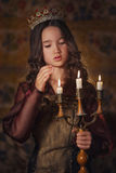 Portret van leuk meisje die een kroon met kandelaar in handen dragen Jonge koningin of prinses royalty-vrije stock foto's