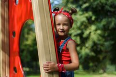 Portret van leuk meisje in enim algemene en rode T-shirt en headscarf het spelen van en het hebben van pret stock afbeelding