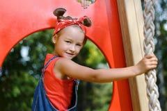 Portret van leuk meisje in enim algemene en rode T-shirt en headscarf het spelen van en het hebben van pret royalty-vrije stock fotografie