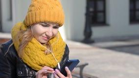 Portret van leuk meisje in hoofdtelefoons die aan muziek luisteren en op mobiele telefoon in stad doorbladeren stock video