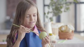 Portret van leuk meisje met schitterend haar in blauwe schort die paasei met een kleine borstelzitting schilderen in de keuken stock video