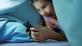 Portret van leuk meisje onder deken met smartphone  stock footage