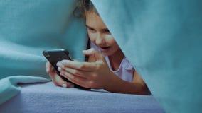 Portret van leuk meisje onder deken met smartphone meisje die online levensstijlspelen spelen onder sociale media stock videobeelden