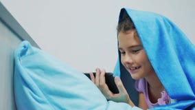 Portret van leuk meisje onder deken met smartphone meisje die online spelen spelen onder een sociale media deken Meisje stock video