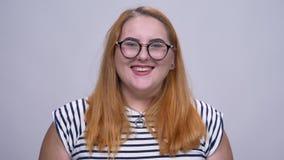 Portret van leuk overweighted roodharig wijfje die met trots en vertrouwen lachen binnen stock footage