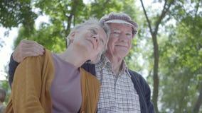Portret van leuk rijp paar in liefdezitting op een bank in het park Aanbiddelijke vrouw en oude man samen offerte stock video