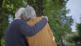 Portret van leuk rijp paar in liefdezitting op een bank in het park Volwassen vrouw en oude man samen offerte stock footage