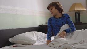 Portret van leuk weinig jongensontwaken in de ochtend met slordig haar en het dragen van pyjama Het kindkielzog omhoog maar wil n stock video
