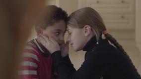 Portret van leuke aanbiddelijke Afrikaanse Amerikaanse jongen en vrij blond Kaukasisch meisje wat betreft voorhoofden elkaar Kind stock videobeelden