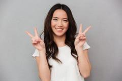 Portret van leuke Aziatische meisjesjaren '20 in toevallige t-shirt en jeans smil Stock Foto's