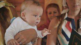 Portret van leuke baby in meterhanden tijdens doopselritueel stock video