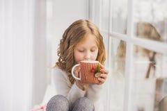 Portret van leuke gelukkige meisjezitting op vensterbank Royalty-vrije Stock Afbeeldingen