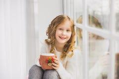 Portret van leuke gelukkige meisjezitting op vensterbank Royalty-vrije Stock Foto's