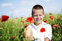 Portret van leuke glimlachende jongen op papavergebied royalty-vrije stock afbeelding